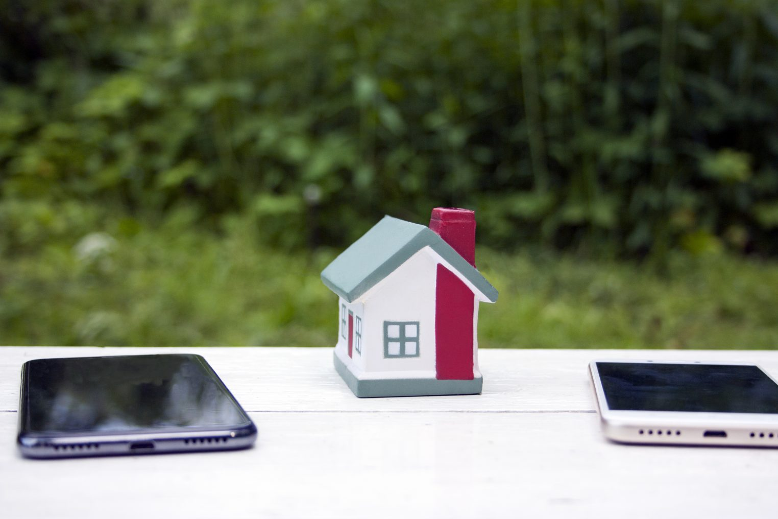 The house stands between two mobile phones - white and black. Conceptual photo. Symbolizes the division of real estate during a divorce. Real estate, investment, mortgage