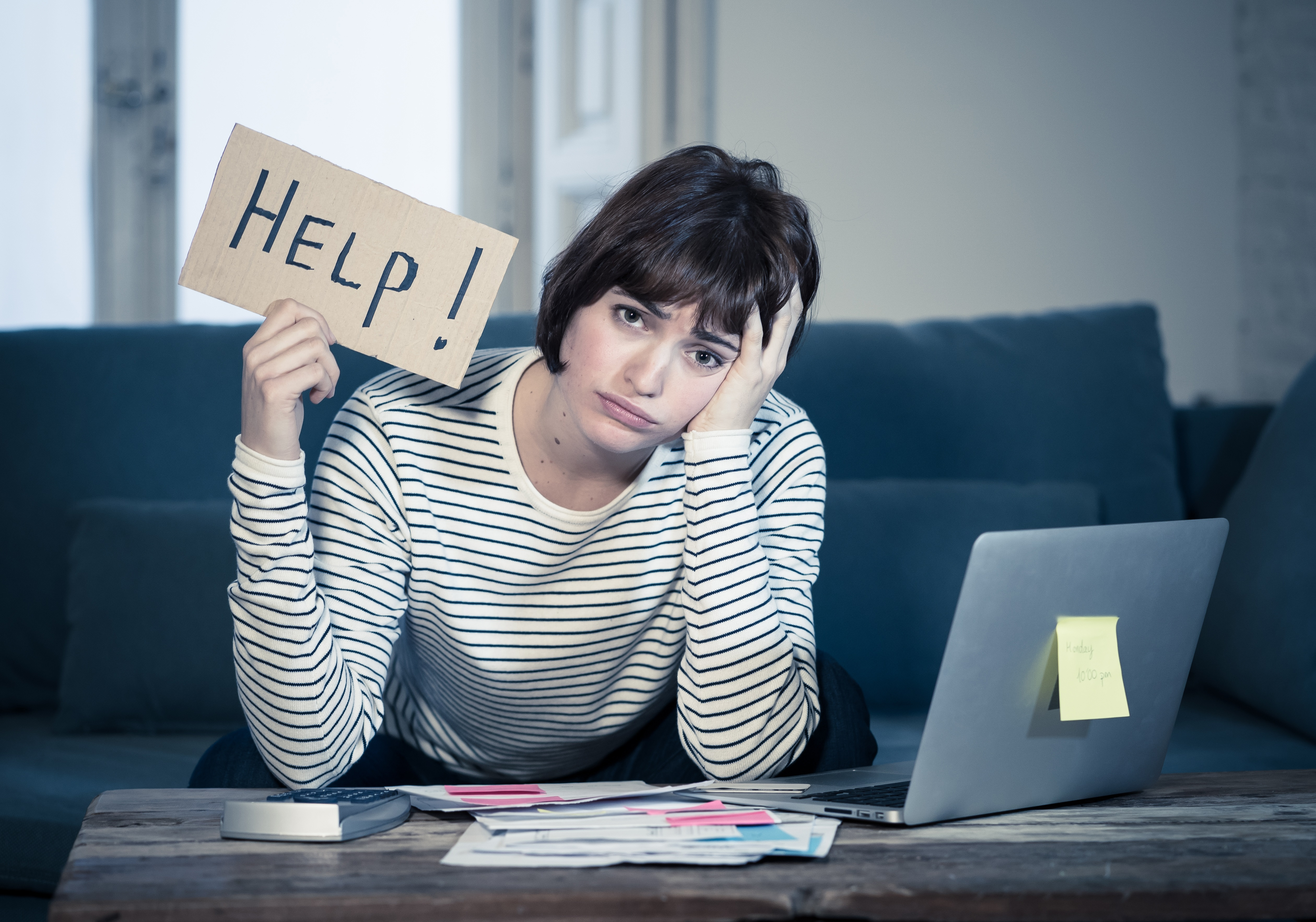Lifestyle portrait of stressed and overwhelmed young woman accounting home finances paying bills