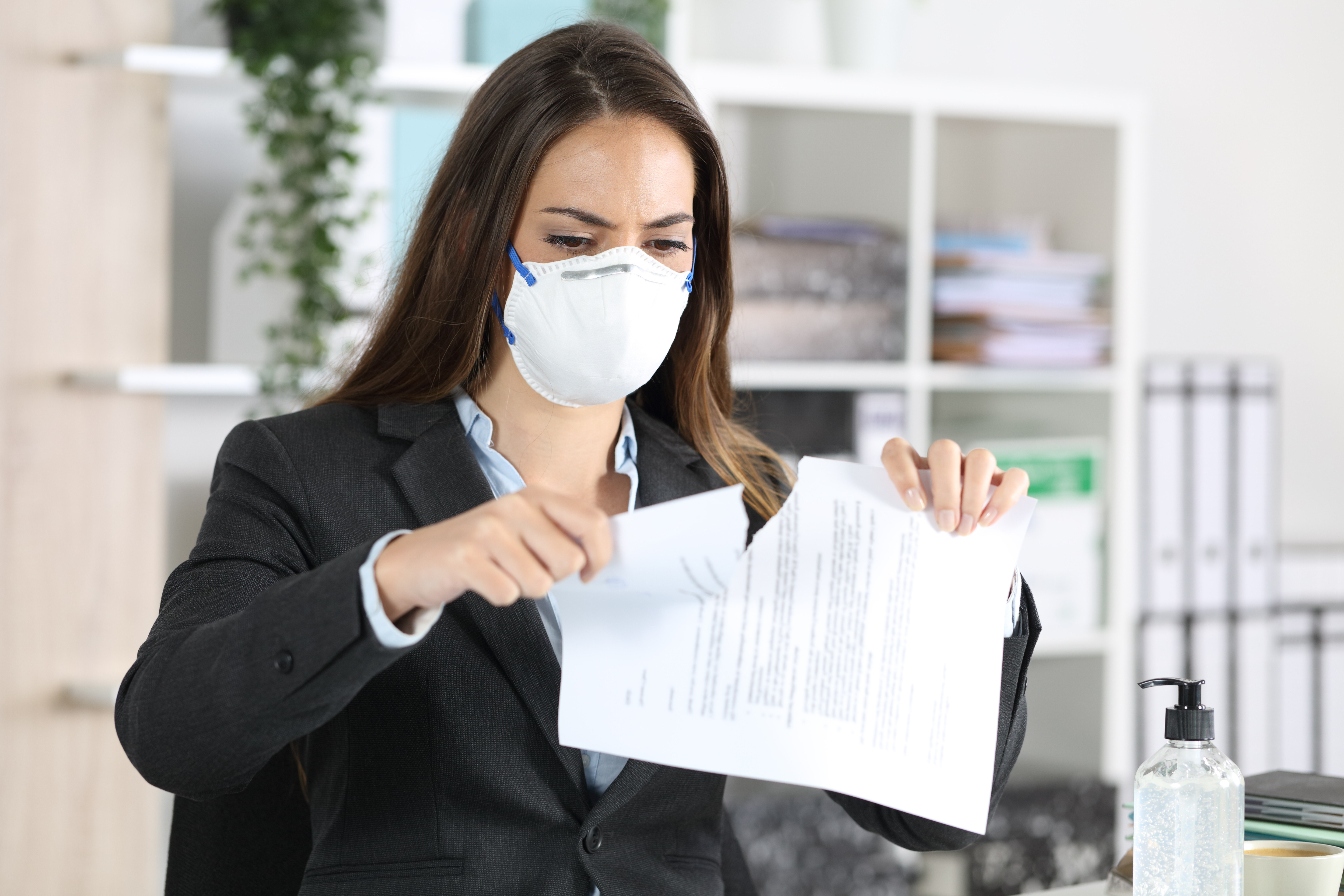 Executive with mask breaking contract at office
